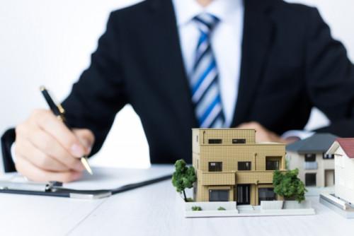 建物の模型の奥で書類に記入する男性