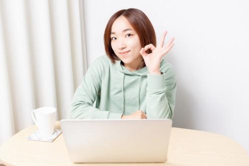 ノート PC の前で OK サインを出す女性