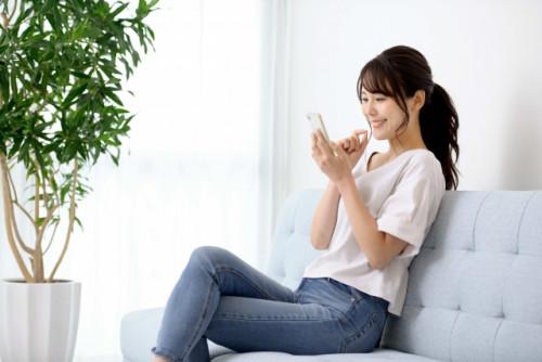 ソファに座って笑顔でスマホを操作する女性