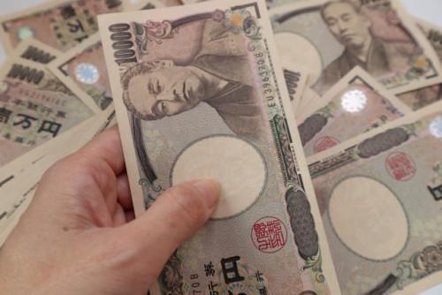 沢山の一万円札の前でその一枚を持つ手